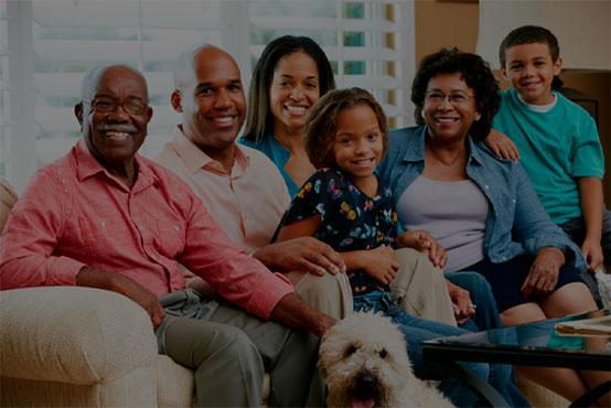 Família reunida no sofa e todos sorrindo