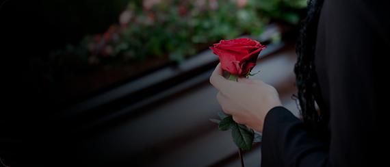 Serviço Funerário - Mulher segurando rosa em um enterro