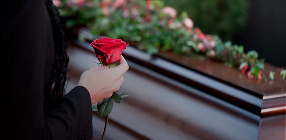 Fotográfia de uma mulher segurando uma rosa em frente a um caixão